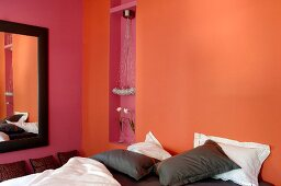 Bed with brown and white pillows against orange-painted wall in modern bedroom