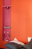 Pillows with dark brown covers against orange wall with mauve niche