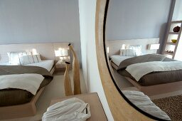 Round mirror on wall opposite modern double bed with pale wooden frame