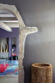 Arched doorway with stone surround and view into colourful modern living room