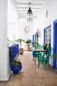 Grüne Stühle vor leuchtend blau lackierten Fensterumrahmungen und Geländer auf der Veranda eines marokkanischen Innenhofs