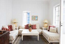 Zimmernische mit dreiseitig aufgestellten Sofas, zentralem Tisch und Lampen mit Kugelfuss