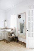 Orientalisches Bad mit gefliestem Waschtisch; gemauerte Dusche und marokkanische Hängelampe im Spiegelbild