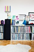 Record collection on shelves against wall & candelabra on speaker