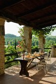 Set table and delicate, metal chairs on roofed terrace with view across Tuscan landscape