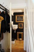 Coat rack in foyer and view of gilt picture frames on black wall and corner sink through open door