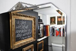 View of gilt picture frames on black wall next to bookshelf above toilet cistern