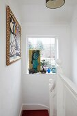 Framed artworks and lattice window in white stairwell
