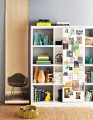Shelving unit with single sliding door covered with pictures; photo of classic chair on long roll of paper decorating wall