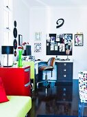 Modern work area with corner desk and swivel chair; spring green couch in foreground next to red chest of drawers