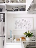 Drawing on wall of white fitted kitchen with stainless steel pots and pans