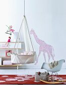 Cradle hanging from ceiling in front of ornaments on shelves and floral silhouette of giraffe on wall