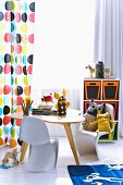 Curtain with pattern of coloured circles, retro table and cuddly toys on child's version of classic Panton chair