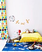 Child's bed below aeroplane silhouettes and colourful clock on wall next to retro curtain with pattern of coloured circles