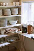 Crockery on simple kitchen shelves next to window