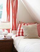 Bedside lamp with ceramic chicken base, red and white patterned curtain and scatter cushions at head of bed
