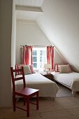 Small, plain white guest bedroom with red accents in attic