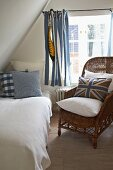Blue-patterned scatter cushions on comfortable bed and wicker chair under sloping attic ceiling