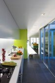 Corridor with white kitchen counter and glass wall leading to wooden terrace; pastel blue door frame and yellow wall add cheerful touches