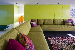 Yellow cupboard doors and purple accents in minimalist living room with enormous corner couch