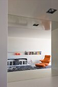 Minimalist bedroom with niche used as bookcase and orange designer armchair