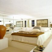 Bedroom decorated in natural shades with double bed on platform next to mirrored wall