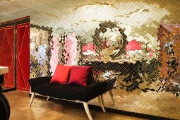 Bench upholstered in black against mirrored mosaic wall next to red interior door