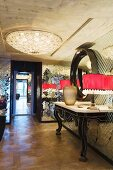 Console table with curved legs and table lamps with red lampshades against mirrored mosaic wall; elegant ceiling lamp on exposed concrete ceiling