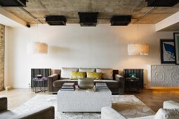 Loft-style interior with cubic coffee table in front of elegant sofa set flanked by designer lamps