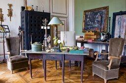 Herrschaftlicher Raum mit rustikalem Tisch und Polstersesseln in künstlerischem, werkstattähnlichem Ambiente