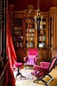 Antike Stühle mit pinkfarbenem Samtbezug vor antikem Einbauschrank und roter Vorhang vor Fenster in herrschaftlicher Bibliotheksecke