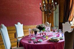 Stühle mit weissem, gepolstertem Bezug auf Rückenlehne um Tisch mit pinkfarbener Tischdecke und Gedecken in Vorbereitung vor rotbraun getönter Wand in herrschaftlichem Esszimmer