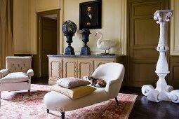 Chaiselongue mit weissem Bezug vor mächtigem Blumenständer aus Stein in griechisch antikem Stil und Sessel in herrschaftlichem Salon