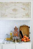 Küchenzeile mit Obstteller und marokkanischen Teegläsern auf Marmorplatte vor gefliestem Spritzschutz unter Hängeschrank mit orientalischem Muster auf Türen