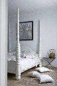 Kissen auf Teppichboden vor Bett mit weiss lackierten gedrechselten Bett-Säulen