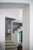 Blick durch Durchgang auf Wendeltreppe mit Trittstufen aus Stein in offenem Treppenhaus
