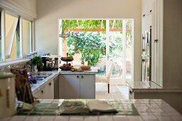 Blick über geflieste Küchenzeile in offener Küche vor Terrassentür und Blick in den Garten