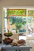 Etagere mit Obst auf gefliester Küchenzeile vor offener Terrassentür und Blick in kleinen Vorgarten
