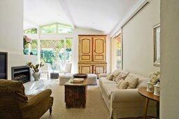 Antiker Sessel und helle Polstercouch vor rustikalem Tisch in modernem Wohnraum eines Hauses