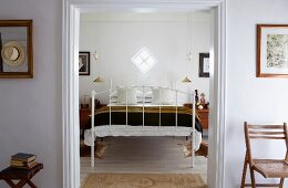 White metal bed below small, lozenge-shaped window; gilt pendant lamps flanking bed
