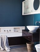 Bathtub & washstand with dark brown wood cladding in bathroom with petrol blue walls