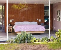 View of bed in sleeping area in glass-walled house