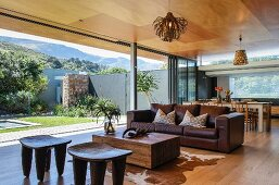 Spacious interior with dining table, seating area & open sliding glass wall leading to garden