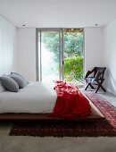 Simple double bed with red blanket on Oriental rug in front of sliding French windows with view into garden