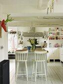 Geräumige Küche mit Mittelblock, weissen Wänden und weiss lackierten Möbeln