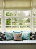 Sitzbank mit Kissen vor einem Fenster mit Gartenblick