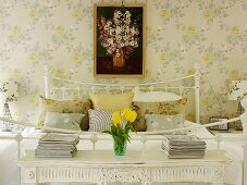 Romantisches Schlafzimmer mit Nachttischchen, Blumentapete und Blumenbild