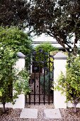 Wrought iron garden gate with floral motif and gravel path leading to house