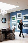 Moderne Kunst an blauer Wand; unter einem großem Lichtfenster ein runder Esstisch und Stühle mit gemusterten Hussen