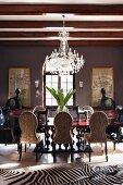Moderne afrikanische Kunst und riesige Blumenvase mit Pflanzenblättern in prunkvollem Essraum mit Zebrafell und Kristallkronleuchter